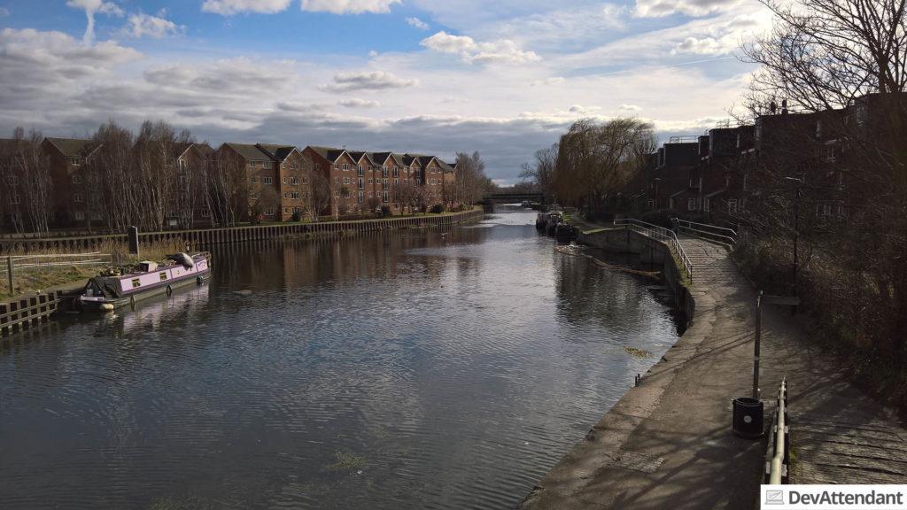 Ein Fluss mit einigen Hausbooten am Ufer; auf der anderen Seite der Brücke gab es noch mehr davon