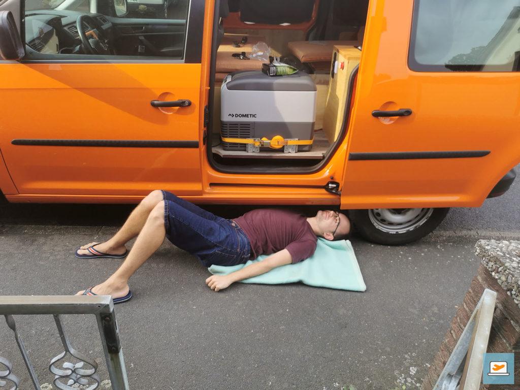 """Aus Beifahrersitz-Perspektive konnte man meiner """"Gymnastik"""" super zuschauen; hier beim Kürzen des Abflussrohres unter dem Auto"""